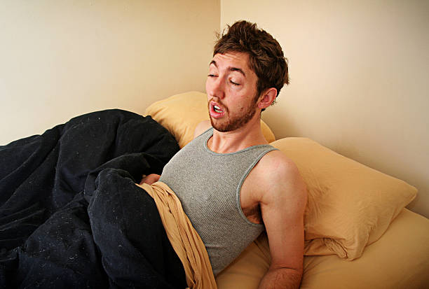 Young Adult Struggles to Wake Up In the Morning A young man is having trouble waking up in his bedroom.  Horizontal with copy space. aftereffect stock pictures, royalty-free photos & images
