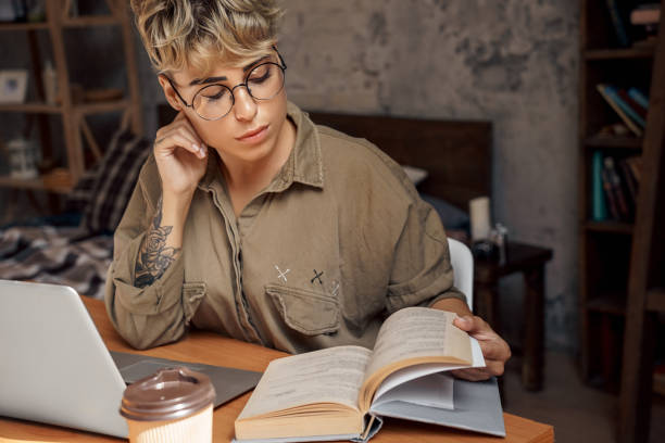 Young adult student girl reading book, sitting behind table stock photo
