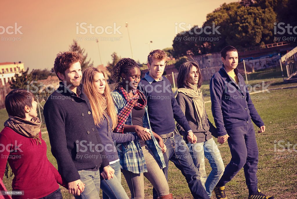 Young adult student outdoors holding hands and walking royalty-free stock photo