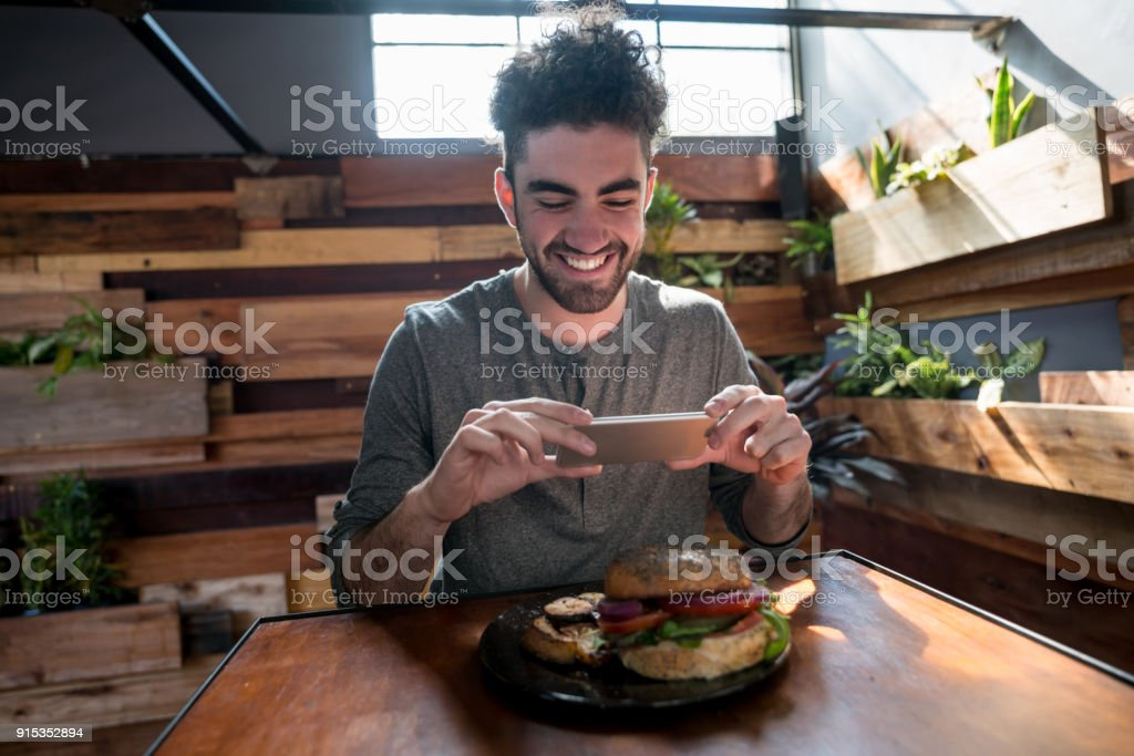 Young adult taking a photo of his dinner to post on his social media stock photo