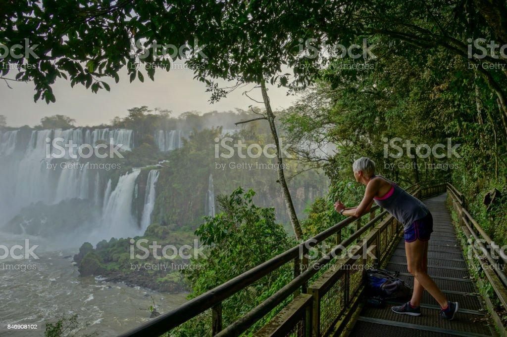 Jovem adulto levando no belo Iguazu cai no Parque Nacional de Iguazu, América do Sul - foto de acervo
