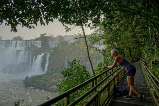 jovem adulto levando no belo iguazu cai no parque nacional de iguazu, américa do sul - belas mulheres argentina - fotografias e filmes do acervo