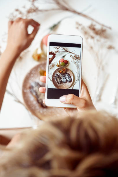 Young adult vlogger making food photo on modern smartphone stock photo