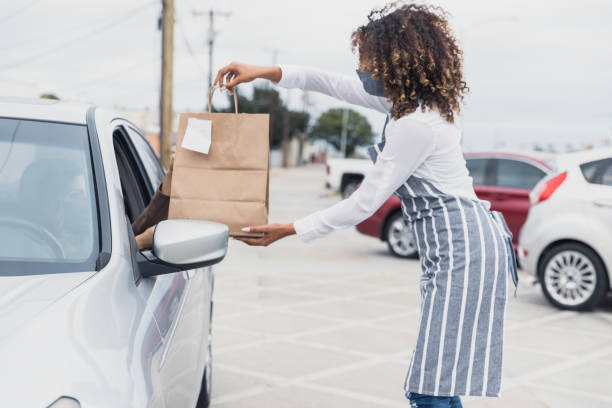 Young adult waitress, wearing mask, social distances to deliver meal A young adult waitress wears her protective mask to deliver a curbside order to an unrecognizable person in a car.  The waitress stands away from the car. curbsidepickup stock pictures, royalty-free photos & images