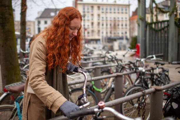 Young adult with long curly red hair unlocking her bike to go to class stock photo