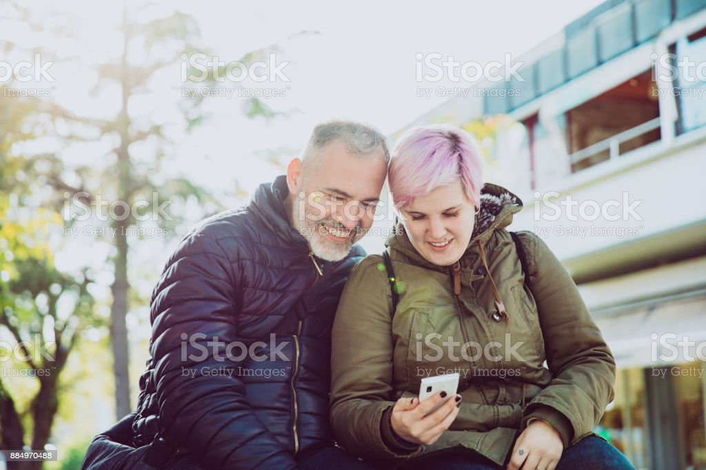 Young Adult Woman and Mature Man Looking at Mobile Phone on Ciy...