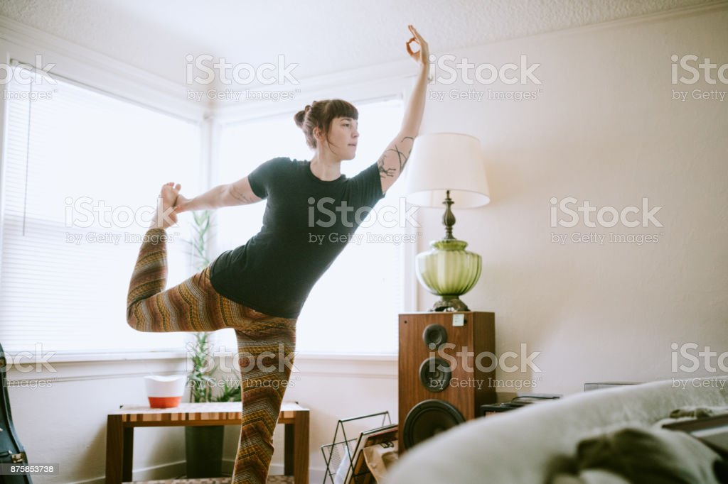 Young Adult Woman At Home Practicing Yoga stock photo