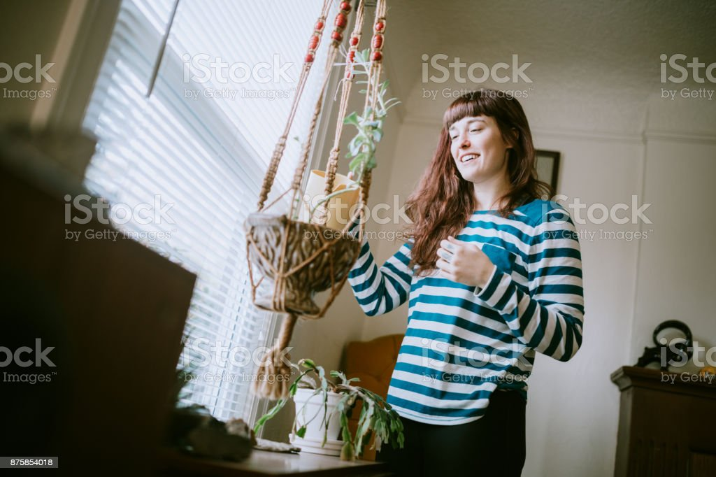 A woman waters her house plants in her living room, the sunlight...