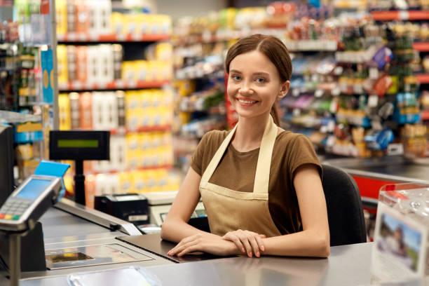 young adult woman cashier on checkout in market - supermarket worker imagens e fotografias de stock
