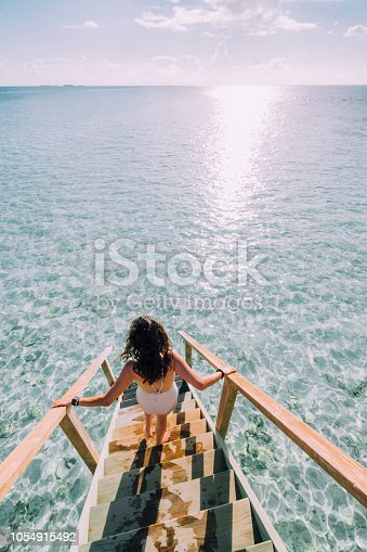 Chasing the sun in Maldives. A staircase going down in the sea.