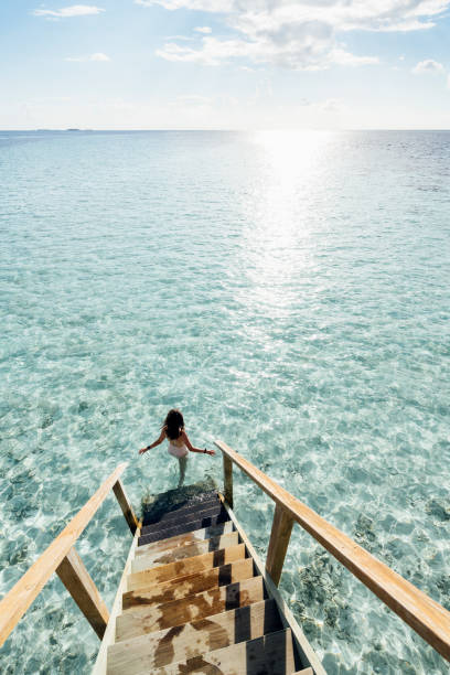 Young adult woman chasing the sun in Maldives stock photo