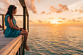 Chasing the sun in Maldives. Looking at sunset sitting on a pier.