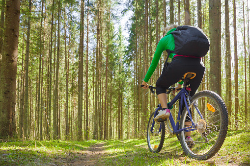 Young adult woman cycling through green forest in fresh air. Backpack on back. Enjoying sport in sunny day. Outdoor activities on weekends. Active recreation in nature. Low angle view.