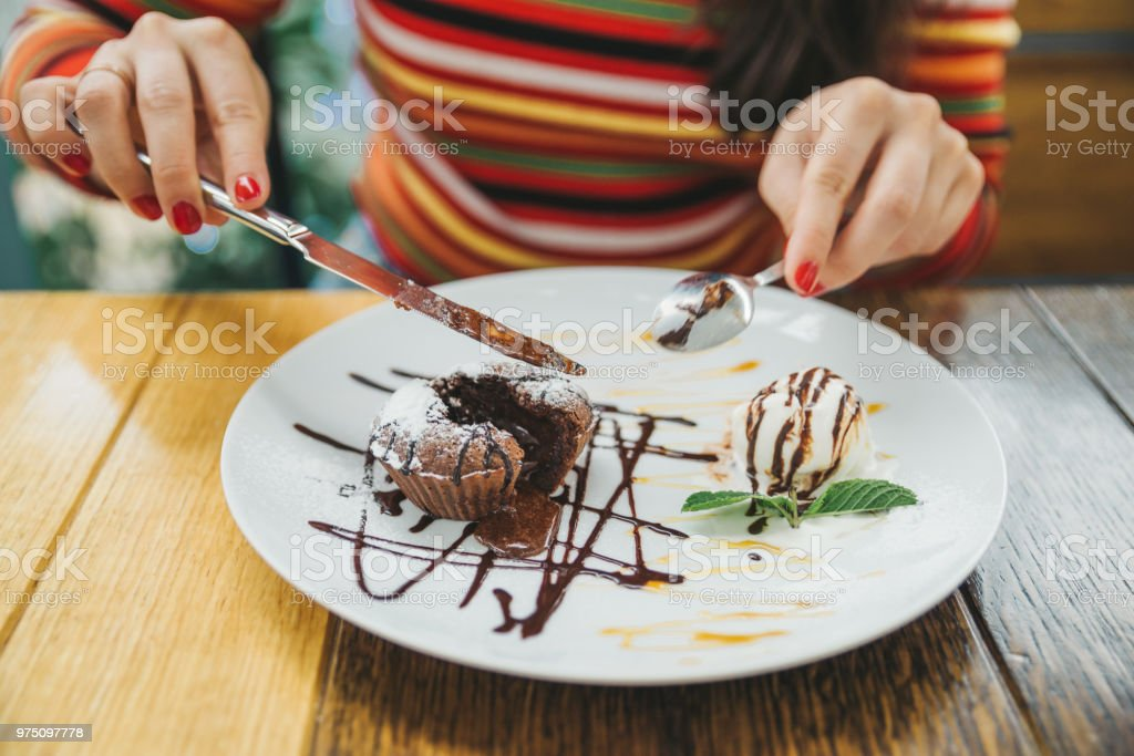 young adult woman eating chocolate fondant in cafe. stock photo