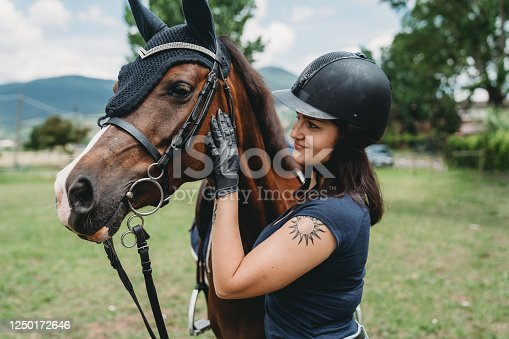 Young adult woman embracing her horse at the riding school. She's stroking the horse. Caucasian ethnicity.