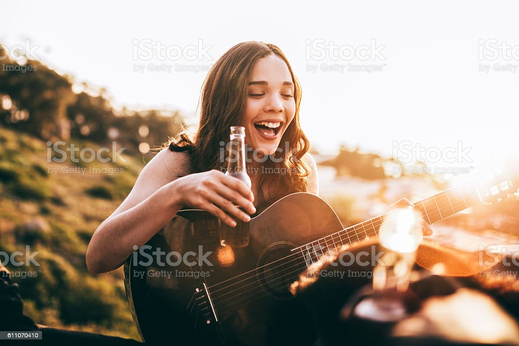 Young adult woman enjoying beer and playing guitar stock photo