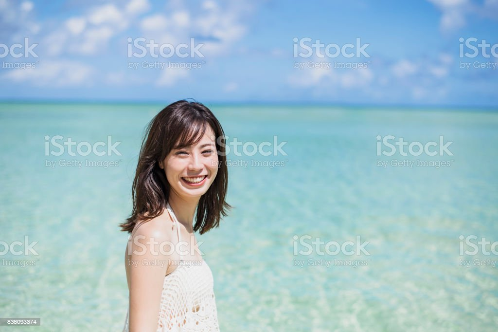 Young adult woman enjoying clear beach in guam stock photo