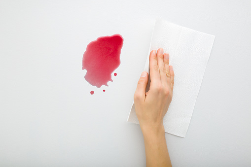 Young adult woman hand cleaning fresh spilled red beverage from light gray table background. Wine stain simple removing with white paper napkin. Closeup. Top down view.