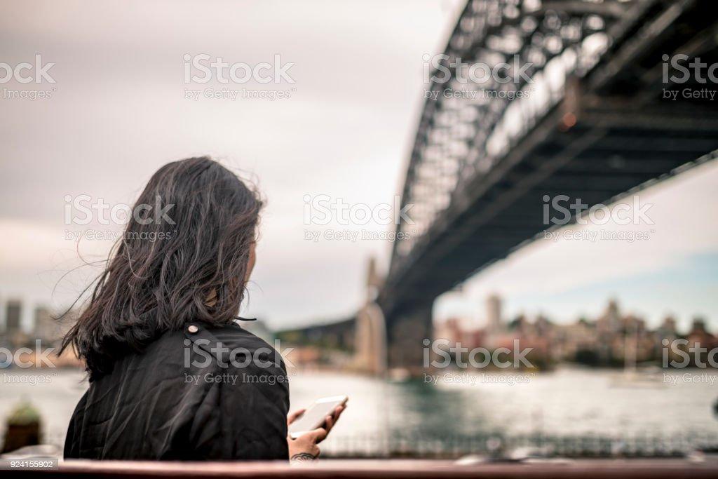 Junge Frau haben eine Pause und schreiben etwas auf Smartphone neben Sydney Harbour Bridge – Foto