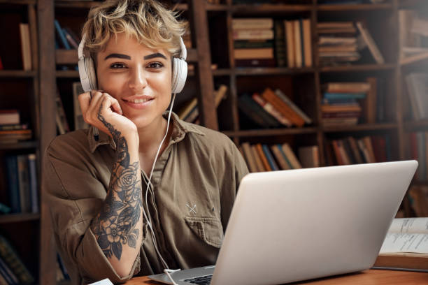 Young adult woman in headphones looking at camera stock photo