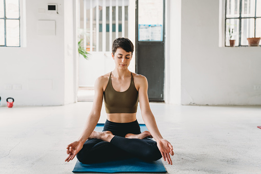 Young adult woman is practicing yoga in a modern loft. Lotus or padmasana pose.