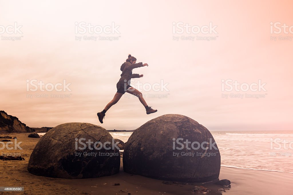 young adult woman jumping on Moeraki Boulders, South Island New stock photo