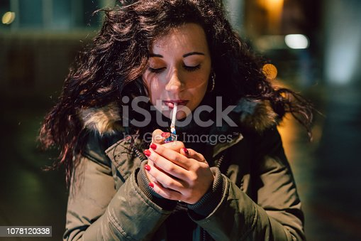 Young Adult Woman Lighting Cigarette In The City At Night