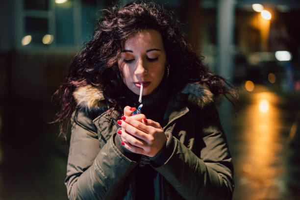 Young Adult Woman Lighting Cigarette In The City At Night stock photo