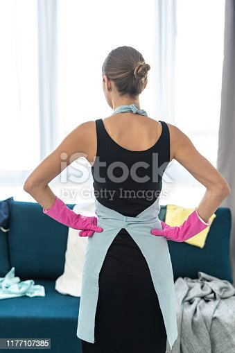 Back rear view of young adult woman holding hands on hips, standing in living room and looking at mess on sofa
