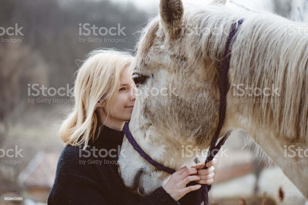 Young adult woman loves her white horse after ride