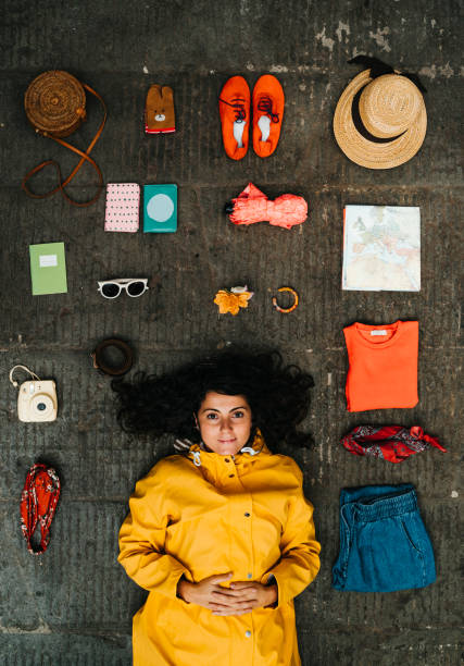 Young adult woman lying down with clothes and various objects Young adult woman lying down with clothes and various objects. There is a generic Europe map with some other stuff all around the young adult woman.   +++Map edited. knolling concept stock pictures, royalty-free photos & images