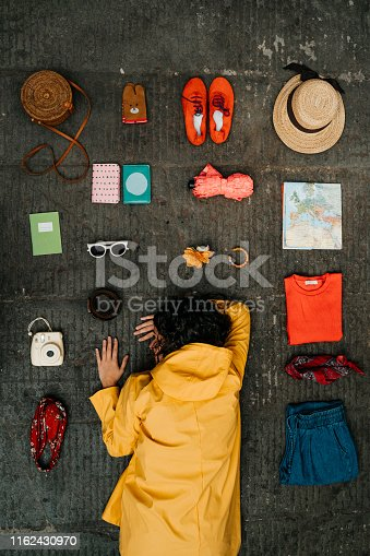 Young adult woman lying down with clothes and various objects