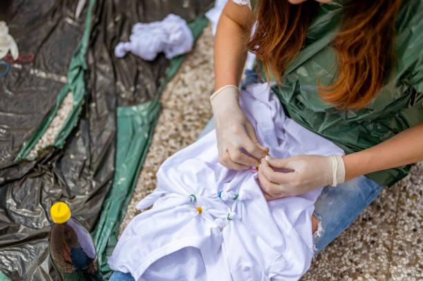 Junge erwachsene Frau macht Krawatte Farbstoff Kleidung im Freien auf dem Dach – Foto