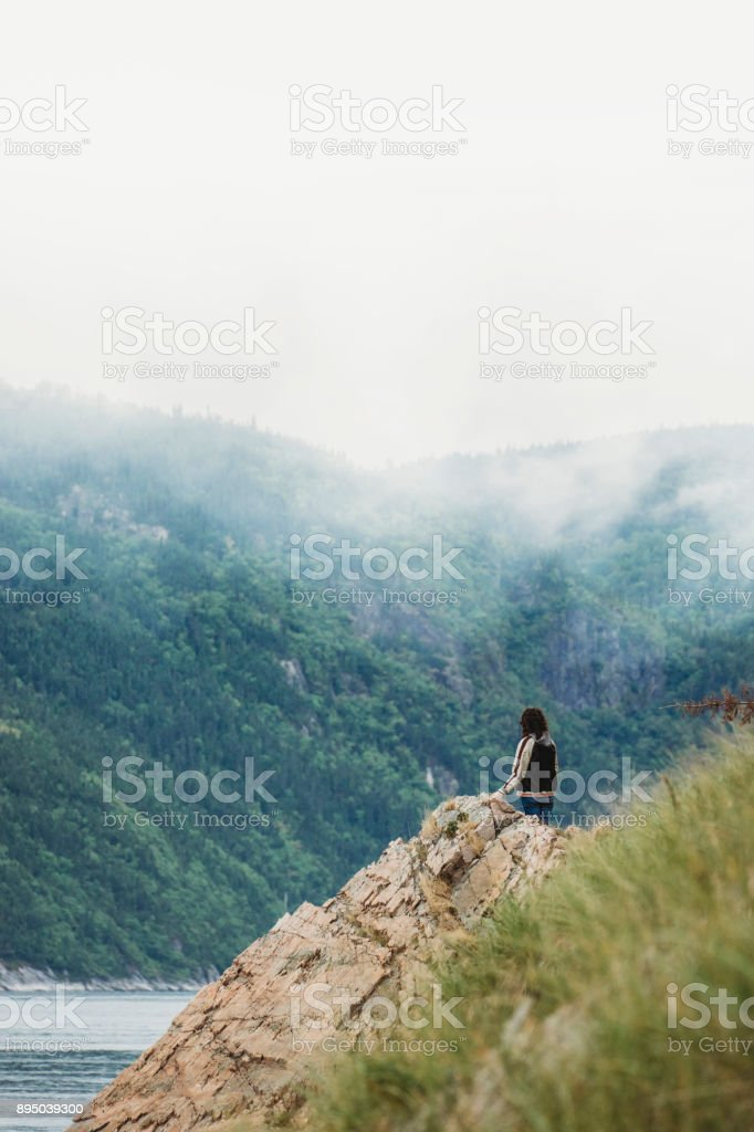 Young adult woman on the coastline looking away stock photo