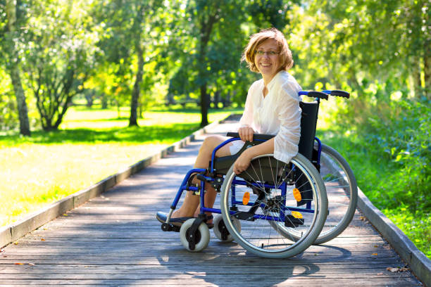 young adult woman on wheelchair in the park stock photo