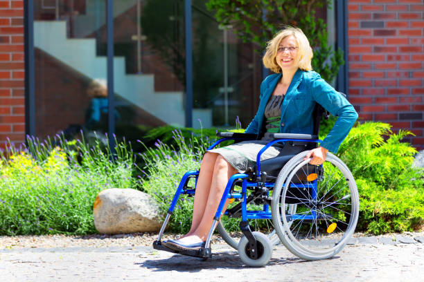 young adult woman on wheelchair on the street stock photo