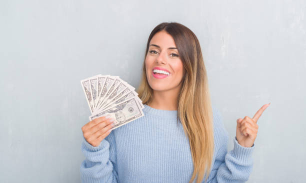 young adult woman over grey grunge wall holding dollars very happy pointing with hand and finger to the side - dollar bill стоковые фото и изображения