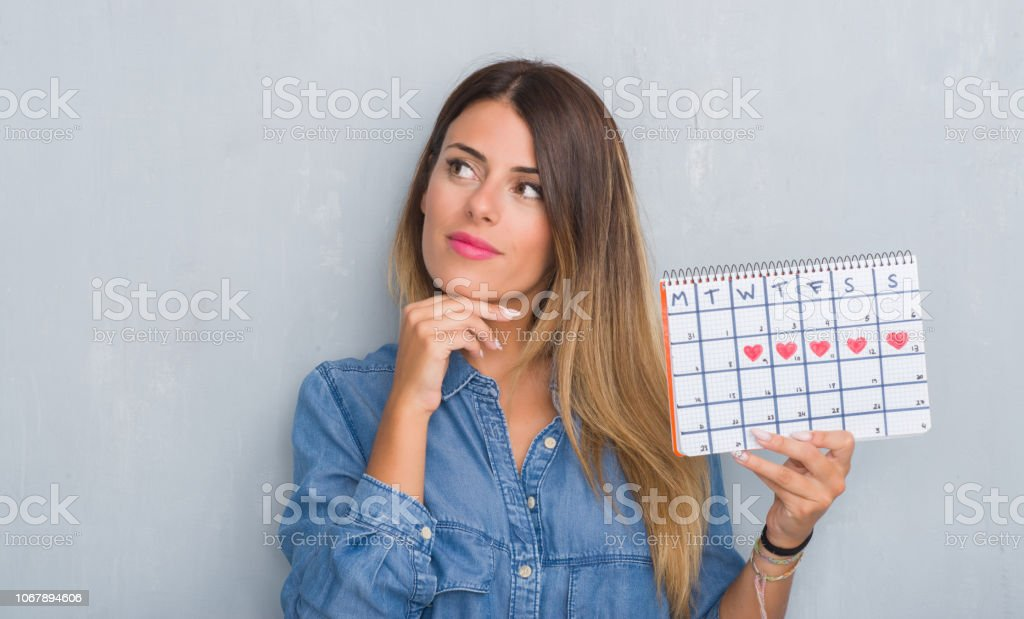 Young adult woman over grey grunge wall showing period calendar...