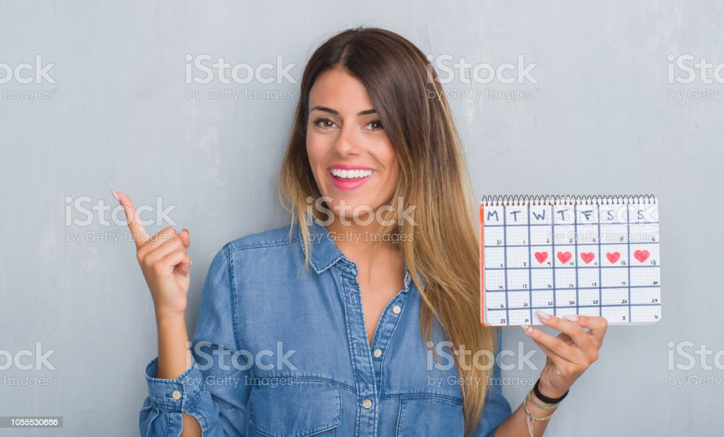 Young adult woman over grey grunge wall showing period calendar very...