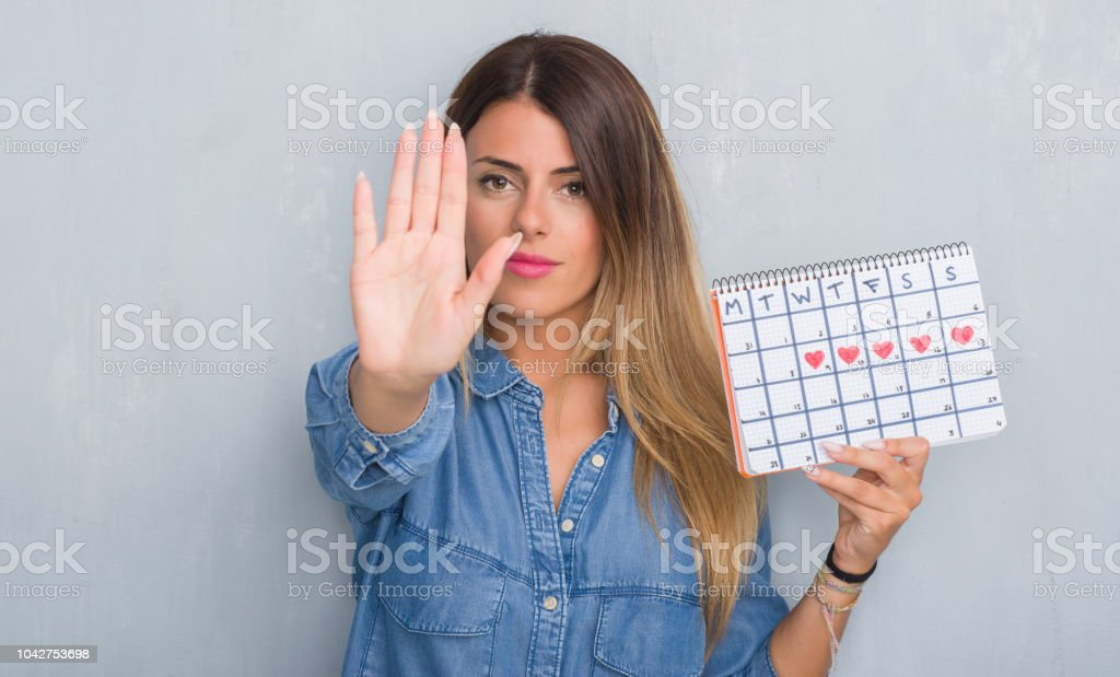 Young adult woman over grey grunge wall showing period calendar with...
