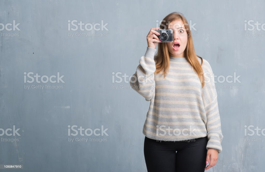 Young adult woman over grey grunge wall taking pictures using vintage...