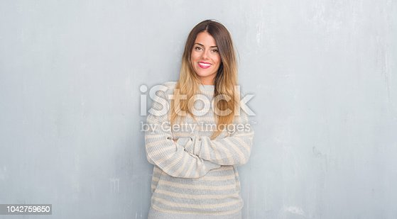 istock Young adult woman over grunge grey wall wearing winter sweater happy face smiling with crossed arms looking at the camera. Positive person. 1042759650