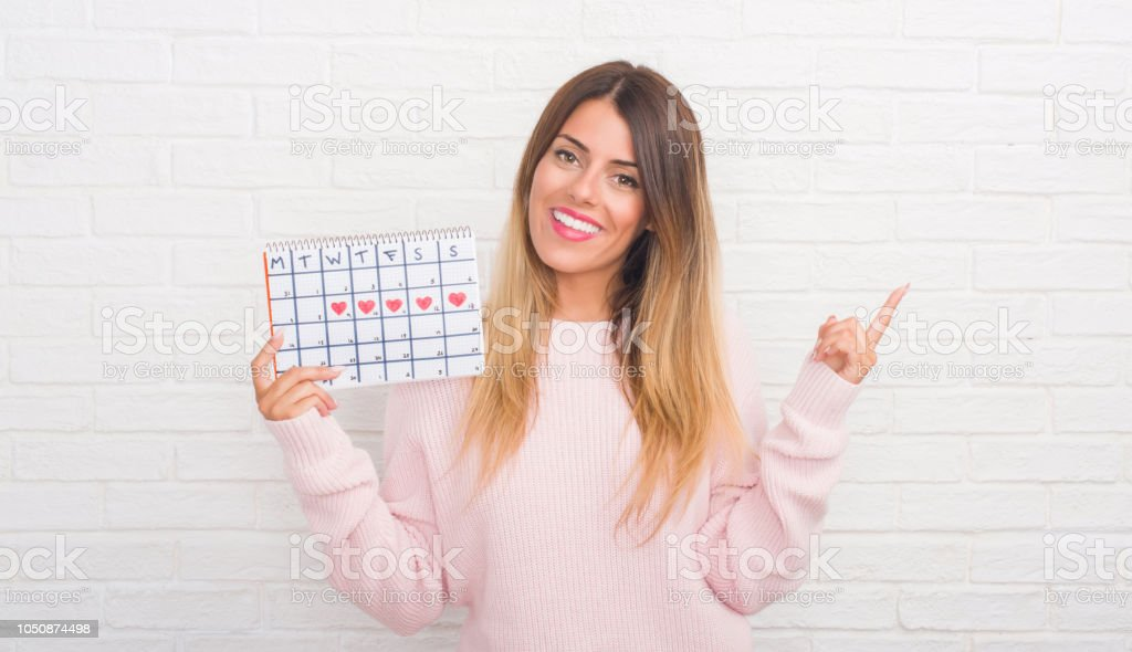 Young adult woman over white brick wall holding period calendar very...