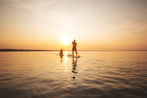 Young adult woman paddle boarding