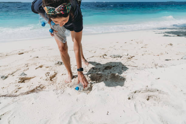 young adult woman picking up some abandoned plastic bottles on the beach - ocean plastic stock pictures, royalty-free photos & images