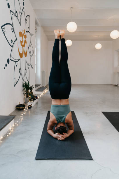 Young adult woman practicing yoga in headstand position Young adult woman practicing yoga in headstand position at the yoga center. Mixed race ethnicity. apanasana stock pictures, royalty-free photos & images