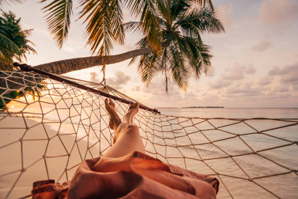 young adult woman relaxing in the hammock at maldives - woman leg beach pov stock photos and pictures