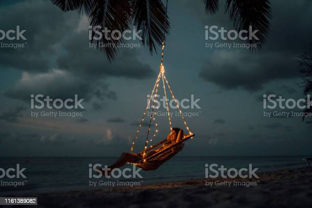 Photo of Young adult woman relaxing on a swing in a tropical paradise