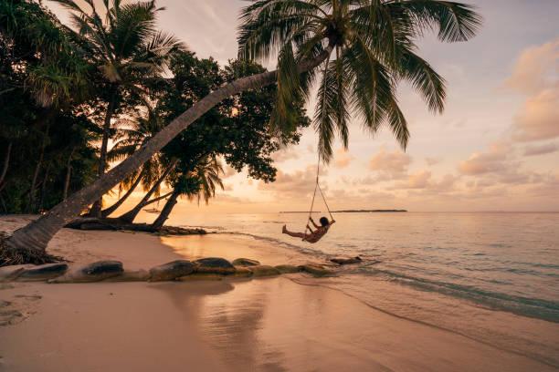 junge erwachsene frau entspannen auf einer schaukel in einem tropischen paradies - idylle stock-fotos und bilder