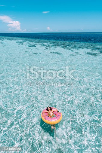 Young adult woman relaxing on inflatable in the sea